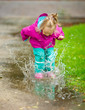 Happy little girl plays in a puddle - 70184821
