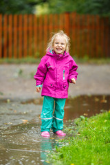 Happy little girl plays in a puddle