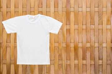 White blank T-shirt on wood texture background