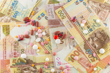 closeup Hong Kong Dollar and pills medicine