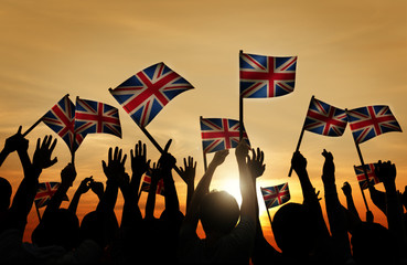 Group of People Waving UK Flags in Back Lit