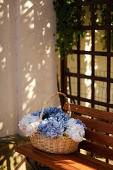 on a wooden bench at the window wicker basket with a bouquet of