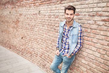 young casual man smilling, leaning on a brick wall