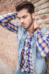 man leaning on wall holding his hand on his neck