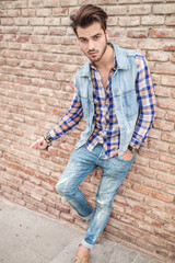man in jeans leaning on a brick wall