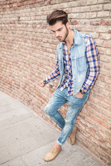 man leaning on brick wall looking down