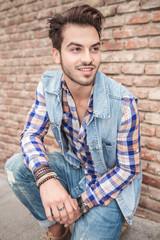 handsome man sitting near a brick wall