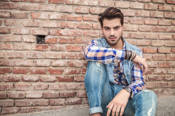 young man sitting near a brick wall, resting