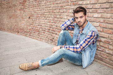 handsome man resting on the sidewalk, leaning against a wall