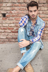 young man sitting on the sidewalk
