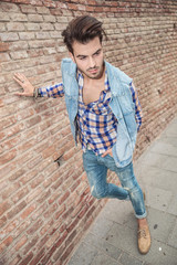 man leaning with one hand on a brick wall