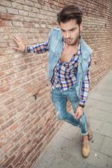 fashion man leaning on a brick wall