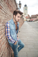 young man leaning on a brick wall