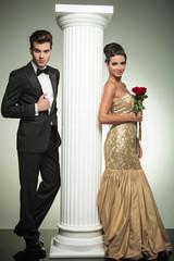 full body picture of an elegant couple near column