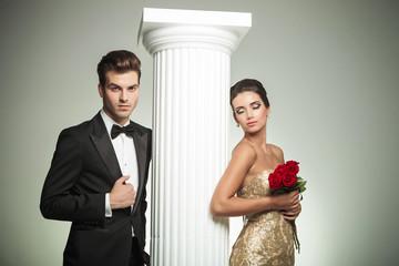 elegant couple posing near column