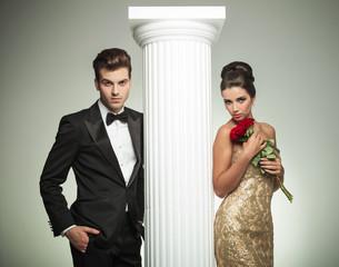 elegant young couple posing near column
