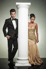 attractive elegant couple posing near column in studio