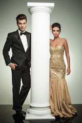 luxury couple posing in studio near column