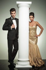 formal man and woman in evening clothes near column