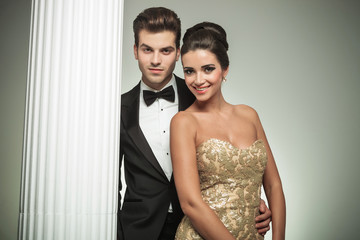 elegant fashion couple smiling together near column