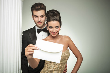 happy young couple presenting an invite to their wedding