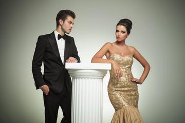 elegant man in tuxedo looking at her sexy woman posing