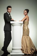 happy elegant couple leaning ona column