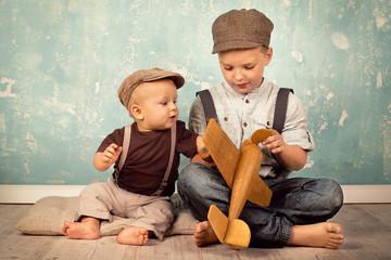 Geschwister spielen mit Holzflieger