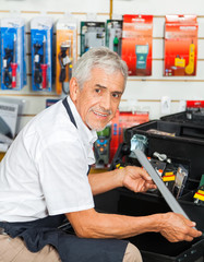 Salesman Holding Tool In Hardware Store