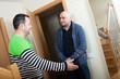 man meeting another man at  door