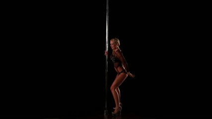 Sexy female pole dancing on black background