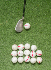 Old golf balls and iron on artificial grass.