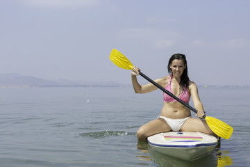 young woman sitting on a paddle board