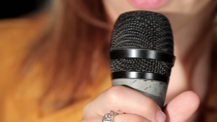 Woman singing at microphone close up
