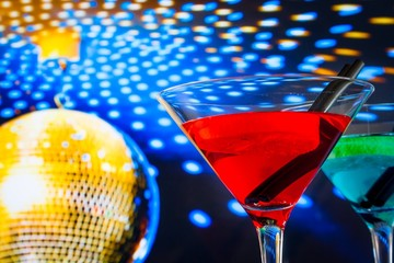 red cocktail with gold sparkling disco ball background