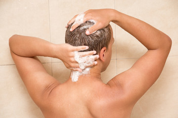 back view of young man washing hair in shower