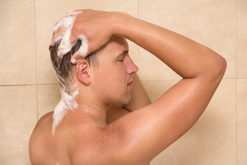 young attractive man washing hair in shower
