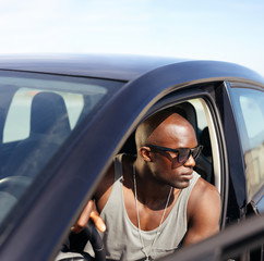 Afro american guy sitting in his car