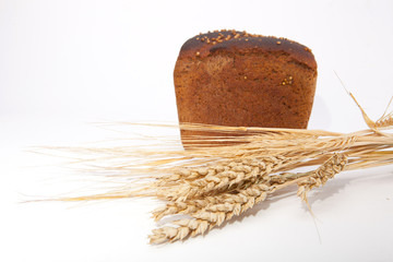 Sliced loaf of bread and wheat ears