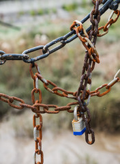 barrier formed by set of old chains with padlock