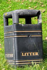 damaged trash bin on a grass bank