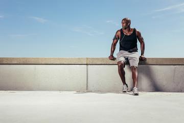 Male runner relaxing on embankment looking away copyspace