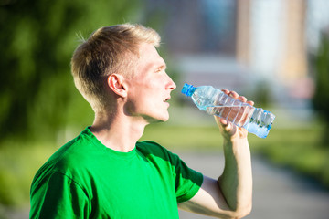 Tired man drinking water from a plastic bottle after fitness