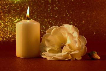 Brennende Kerze und Rose vor goldenem Hintergrund
