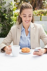 Beautiful businesswoman having a coffee and muffin