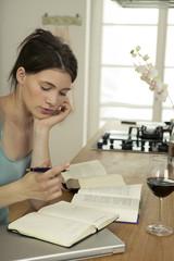 Junge Frau mit Bücher in der Küche,die Hand am Kinn