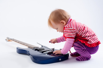 Little girl playing with guitar