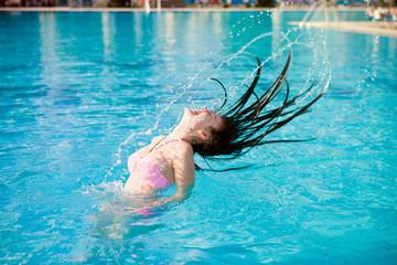 Девушка в бассейне брызгает длинными волосами