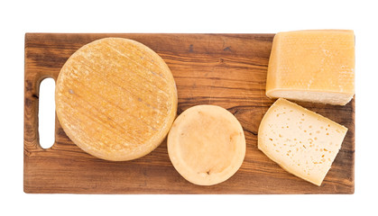 Farm produced organic cheeses on wooden board, isolated on white