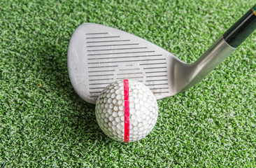 Close up, Old golf balls and iron on artificial grass.
